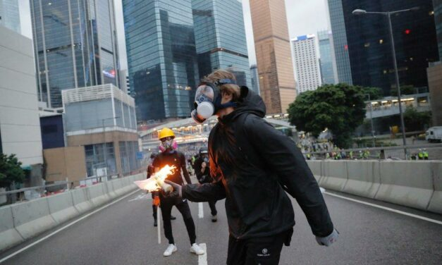 WAR! Hong Kong on lockdown after student, 18, SHOT in chest by cop and another officer threatens to throw Molotov cocktails at protesters as streets turned into battlefield